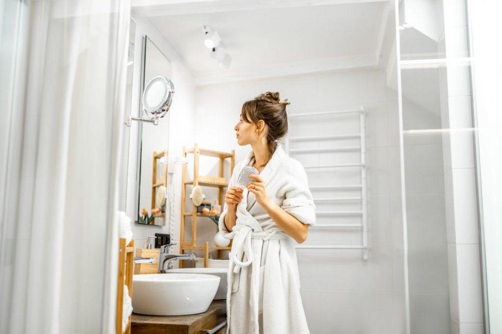 Kobieta przeglądająca się w lustrze zamówionym u firmy Housekrup